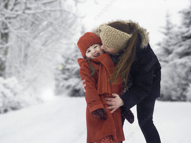 Mother and daughter kissing in snow
