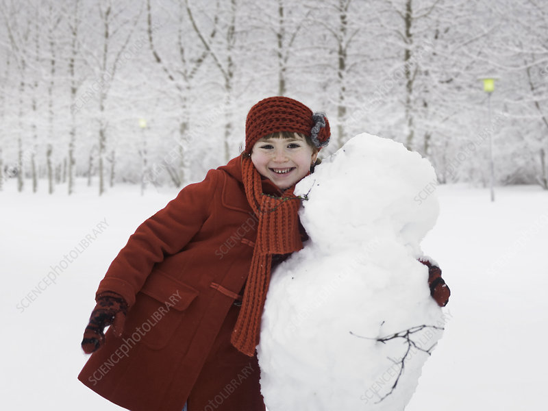 Smiling girl hugging snowman outdoors