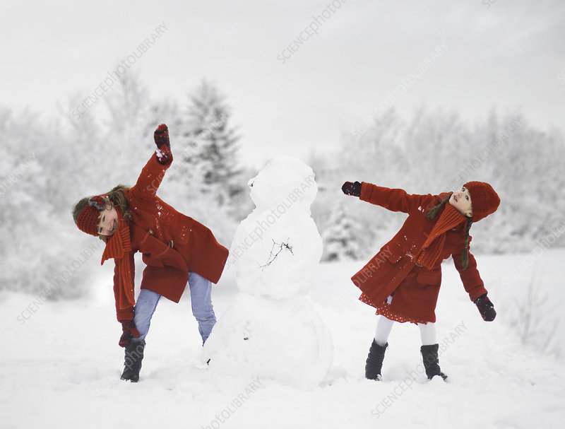 Girls building snowman outdoors
