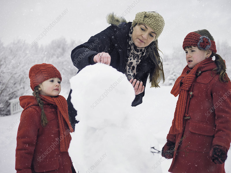 Mother and daughters building snowman