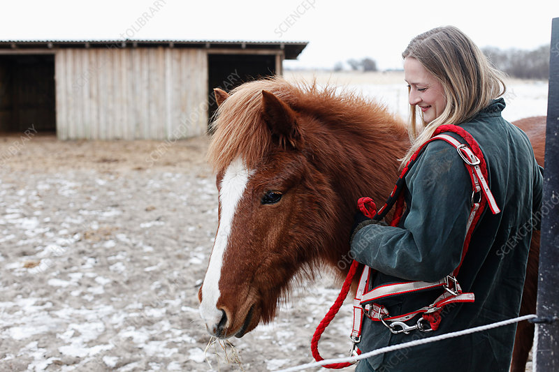 Woman smiling with horse in yard