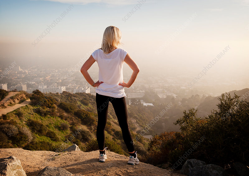 Woman overlooking view from hilltop