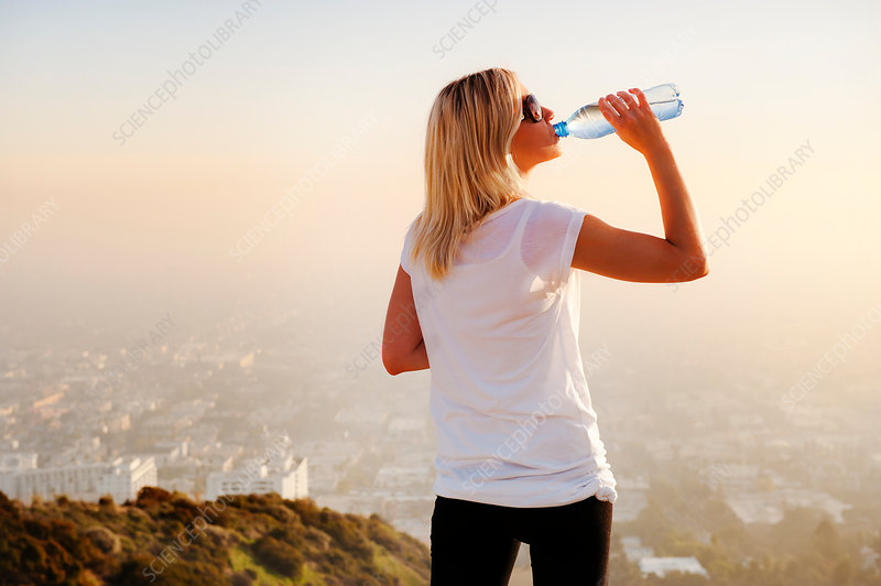 Woman drinking water on hilltop