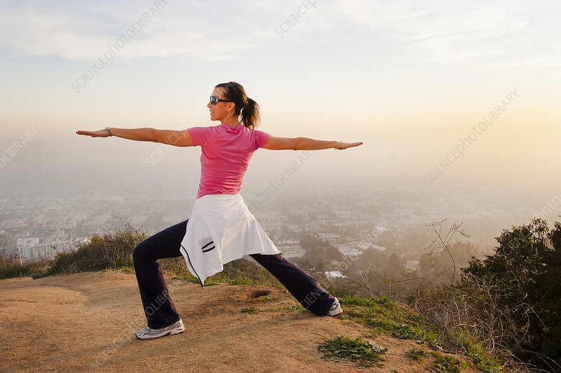 Woman stretching on hilltop