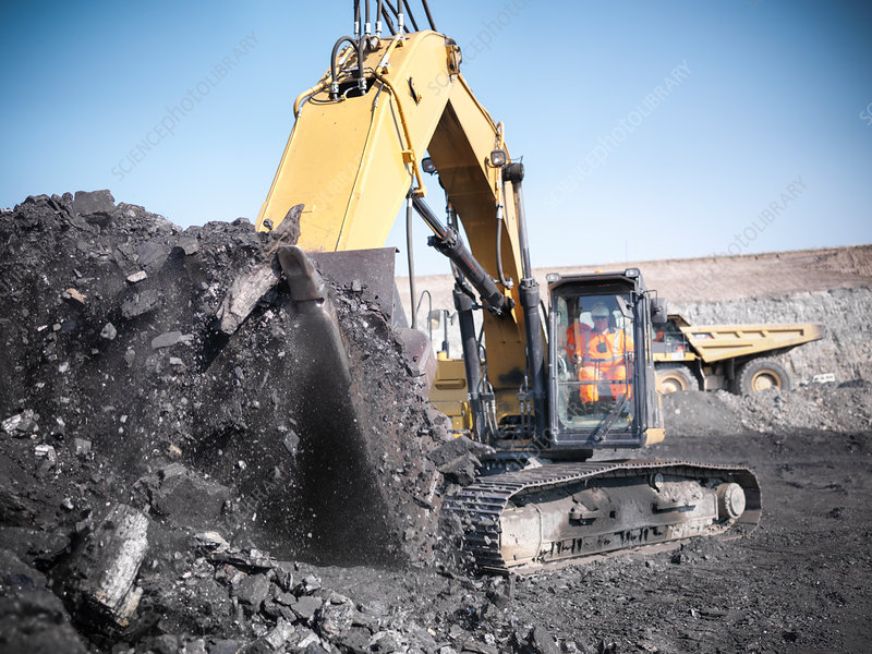 Digger scooping coal at mine