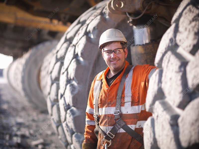 Worker standing by trucks in coal mine
