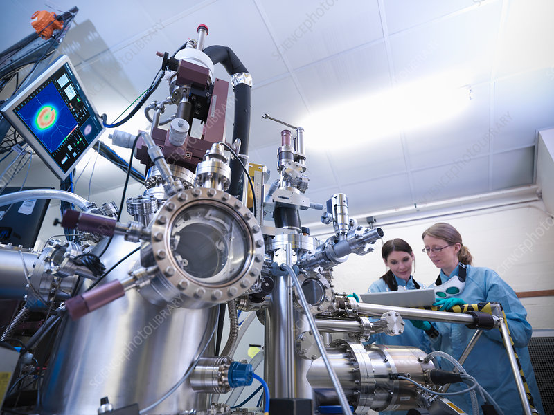 Scientists using vacuum chamber in lab