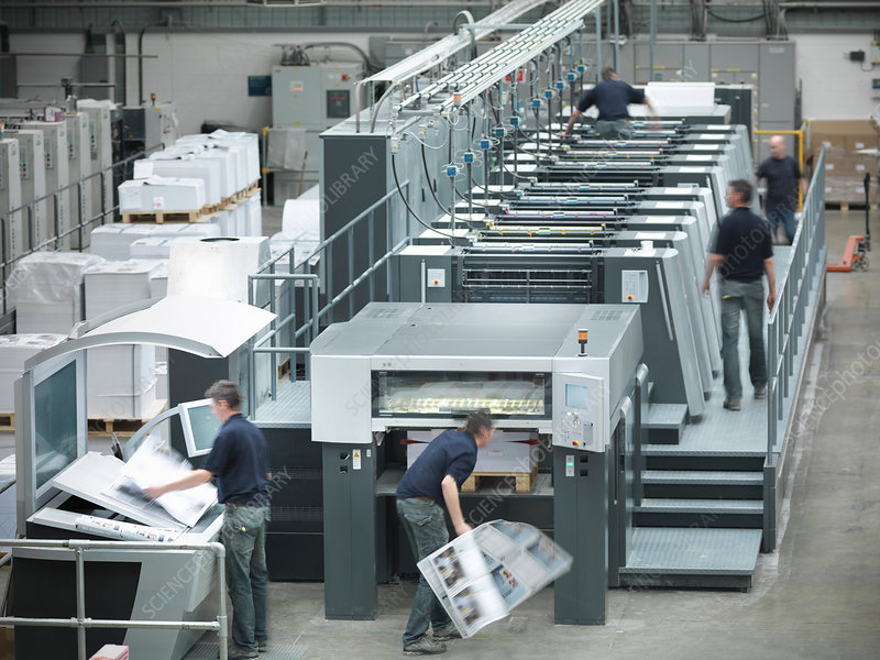 Workers running printing press