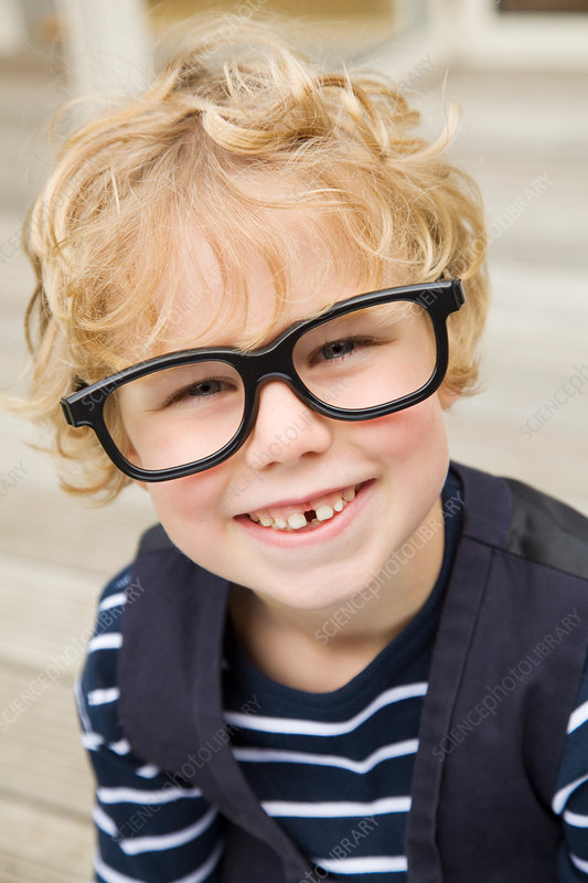 Smiling boy wearing glasses outdoors