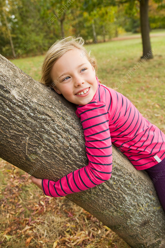Smiling girl hugging tree outdoors