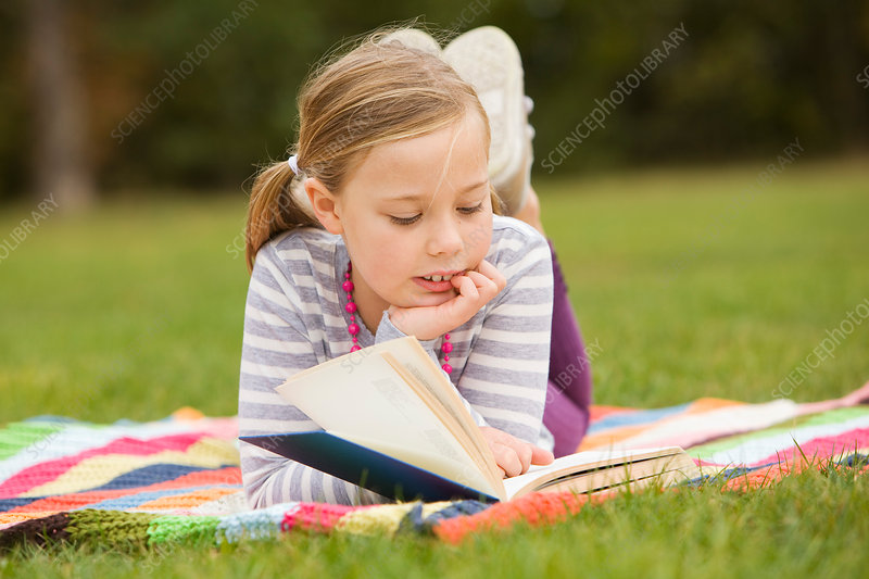 Girl reading book on picnic blanket
