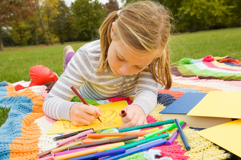 Girl drawing on picnic blanket