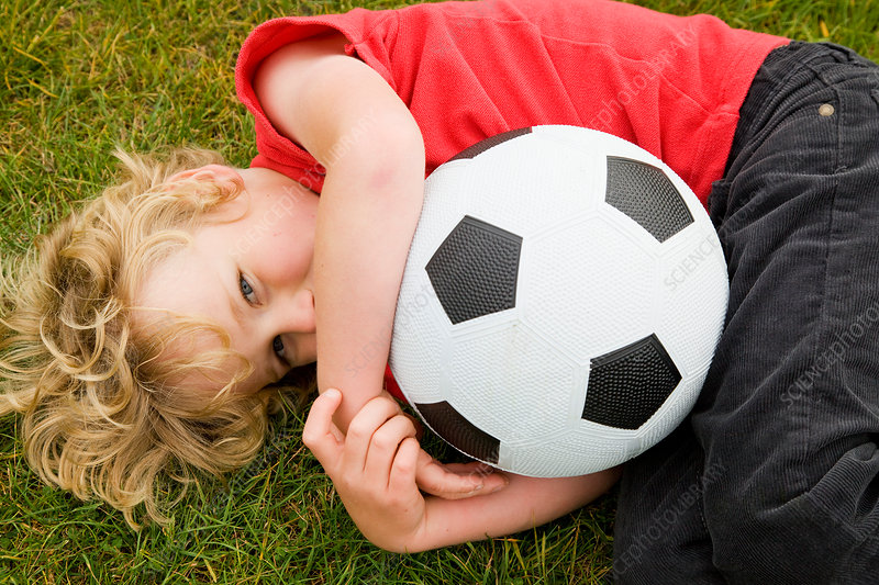 Boy holding soccer ball in grass