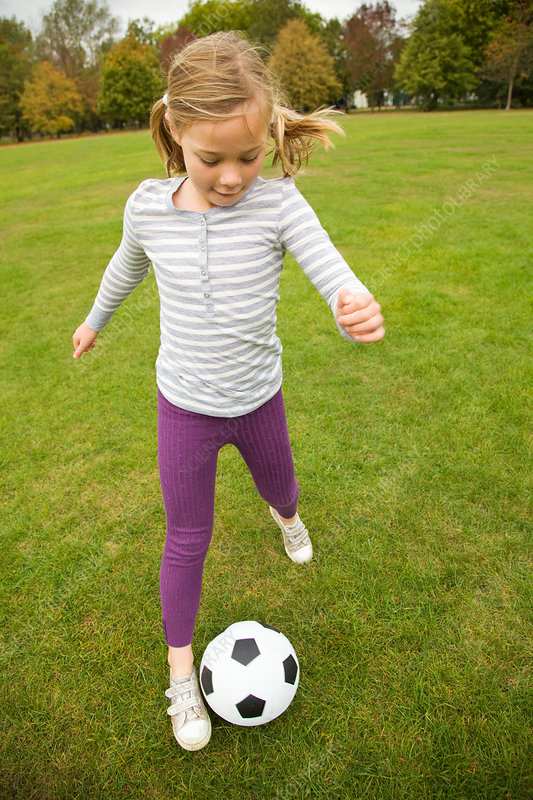 Girl playing with soccer ball in field