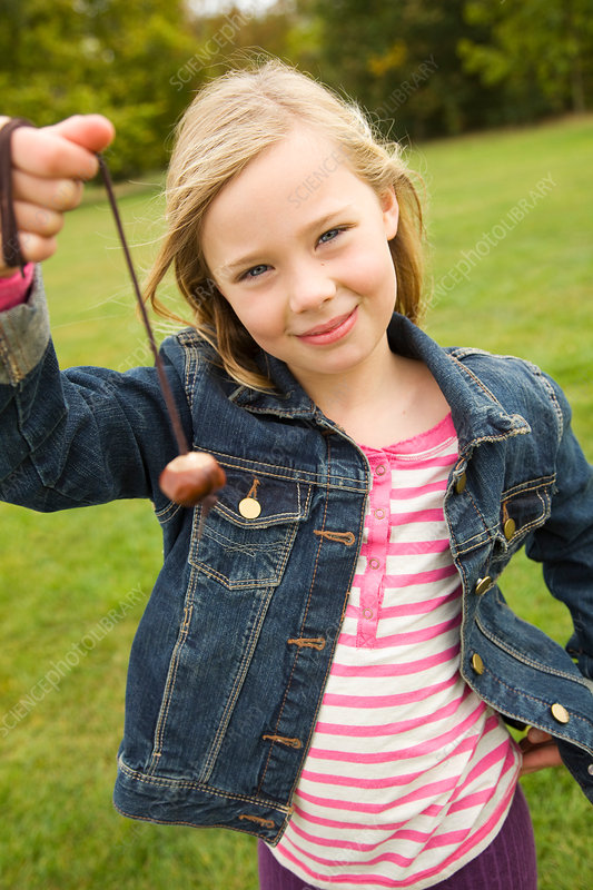Girl playing with chestnut on string