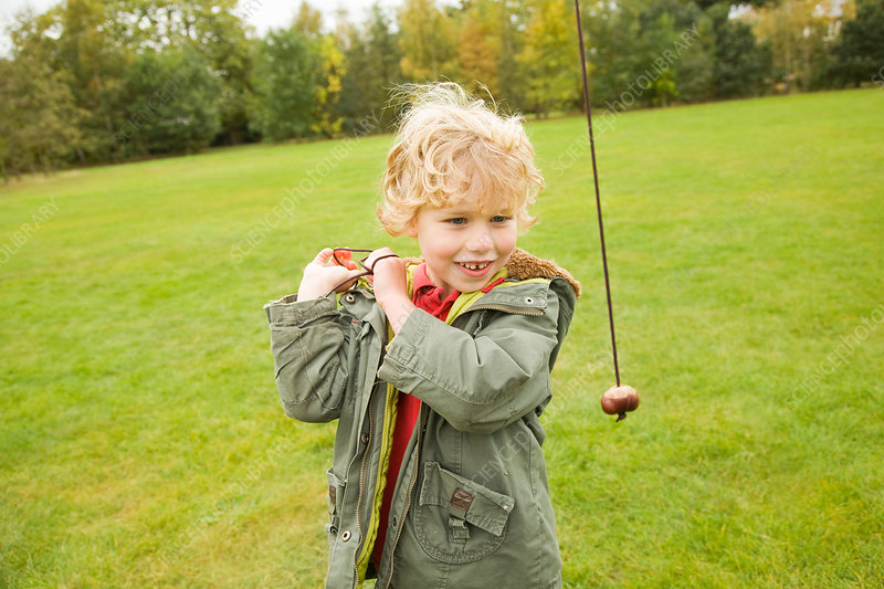 Boy playing with chestnut on string