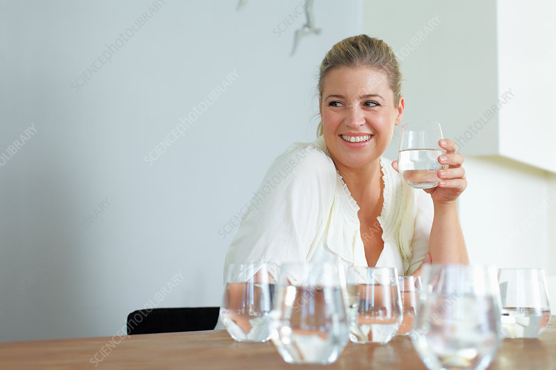 Woman having glass of water at table