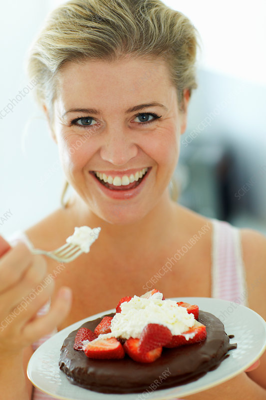Smiling woman eating cake in kitchen