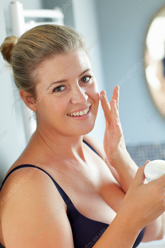 Smiling woman moisturizing her face