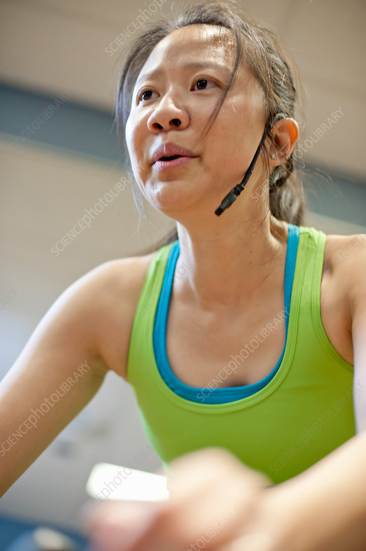 Woman in headset on spin machine in gym