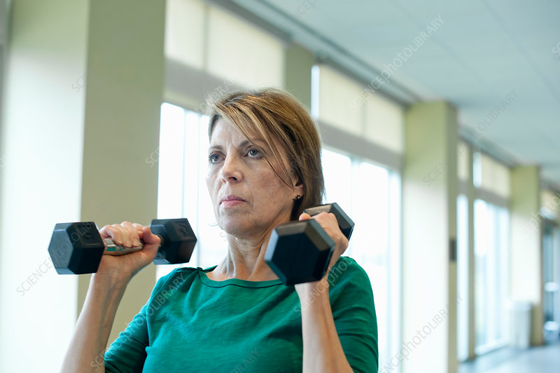 Older woman lifting weights in gym