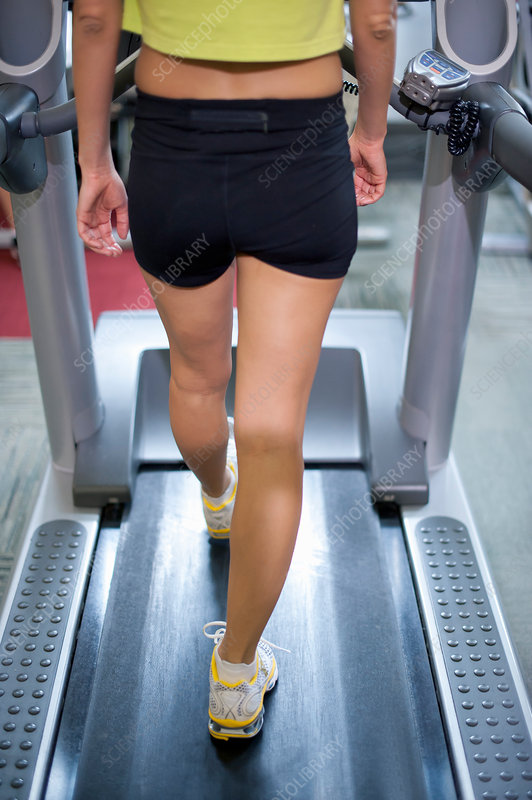Woman using treadmill in gym