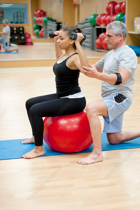 Woman working with trainer in gym
