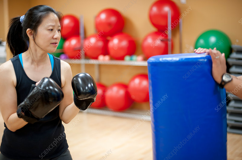 Woman punching bag in gym