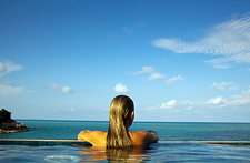 Woman relaxing in infinity pool