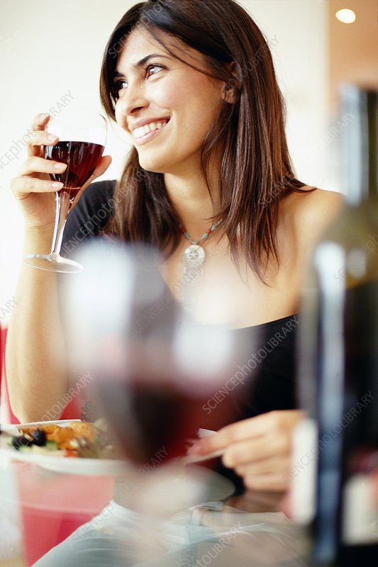 Woman drinking wine with dinner