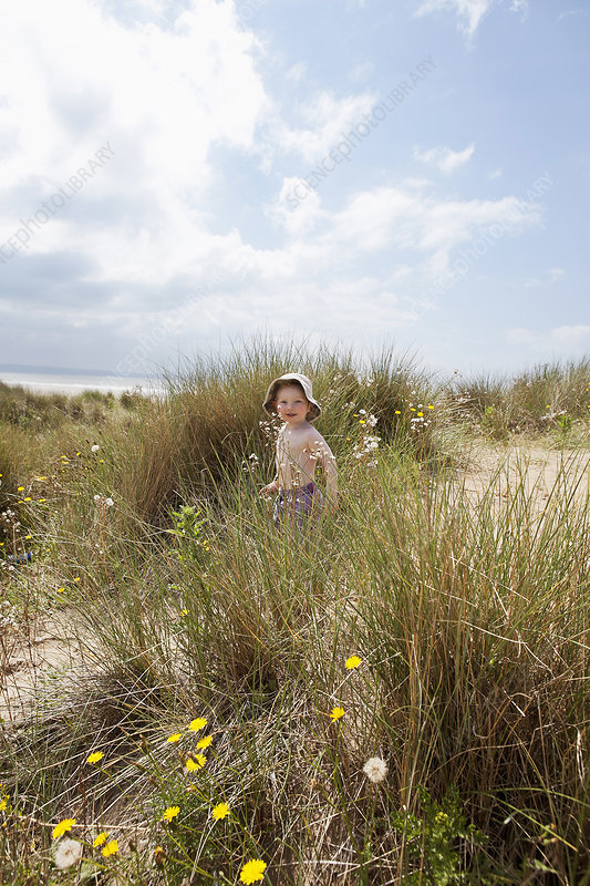 Boy walking in grassy sand