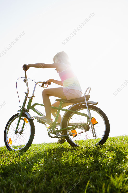 Girl riding bicycle in grass