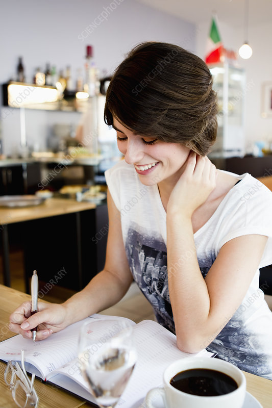 Smiling woman writing in cafe