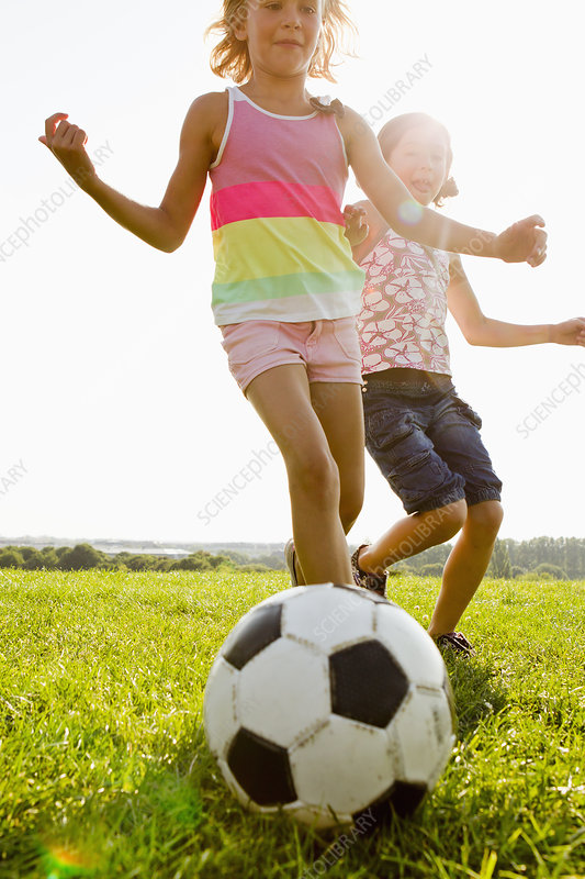 Girls playing soccer in field