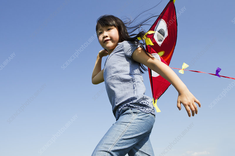 Girl playing with kite outdoors