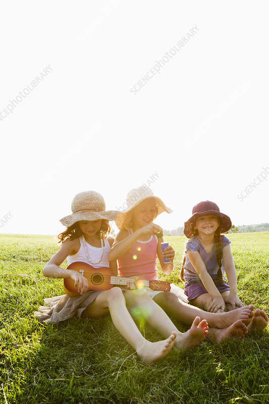 Smiling girls relaxing in grass