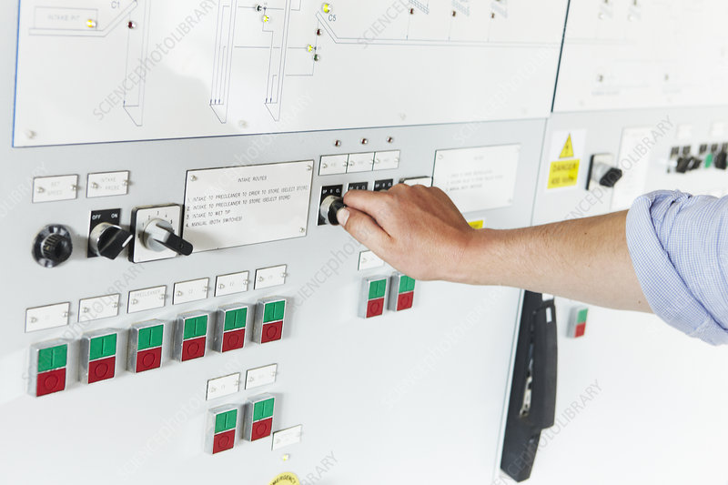Worker adjusting gauge on panel