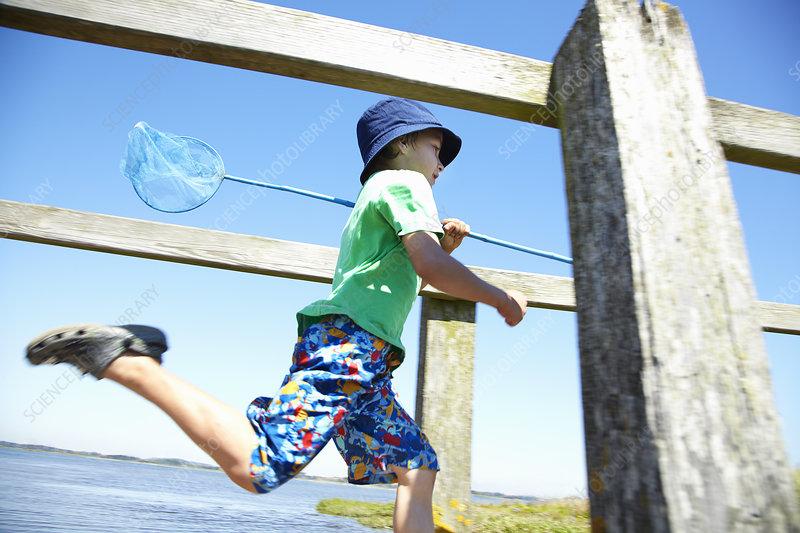 Boy carrying fishing net on dock