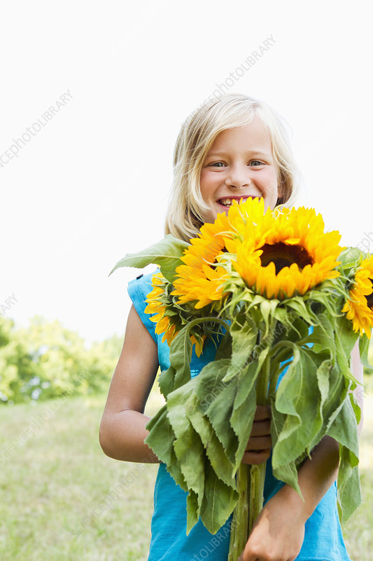 Smiling girl carrying sunflowers