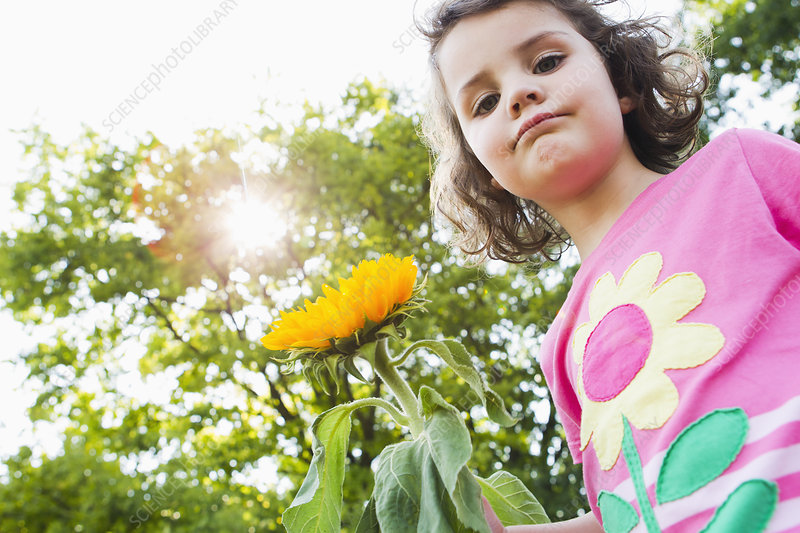 Girl holding wildflower outdoors