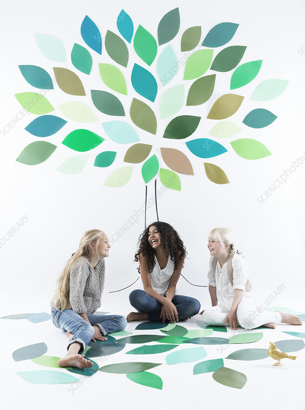Girls talking under tree on wall