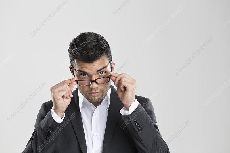 Businessman peering over glasses