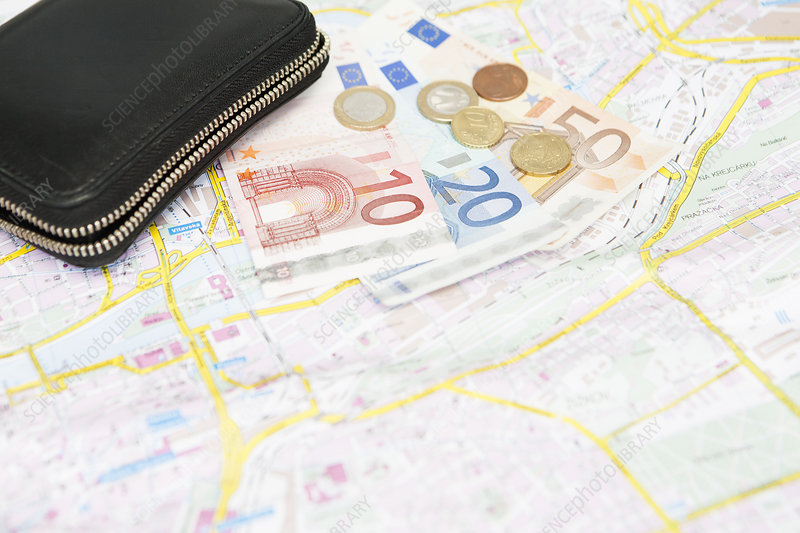 Euro notes and coins on city map
