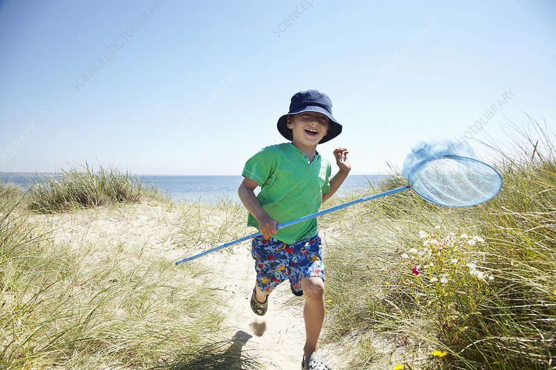 Boy carrying fishing net on beach