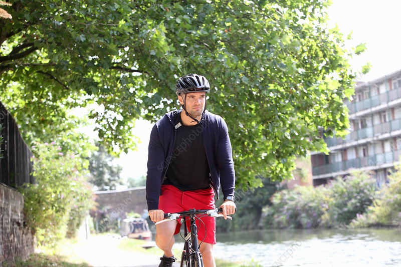 Man riding bicycle by urban river