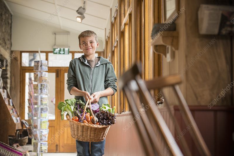 Boy carrying basket of vegetables