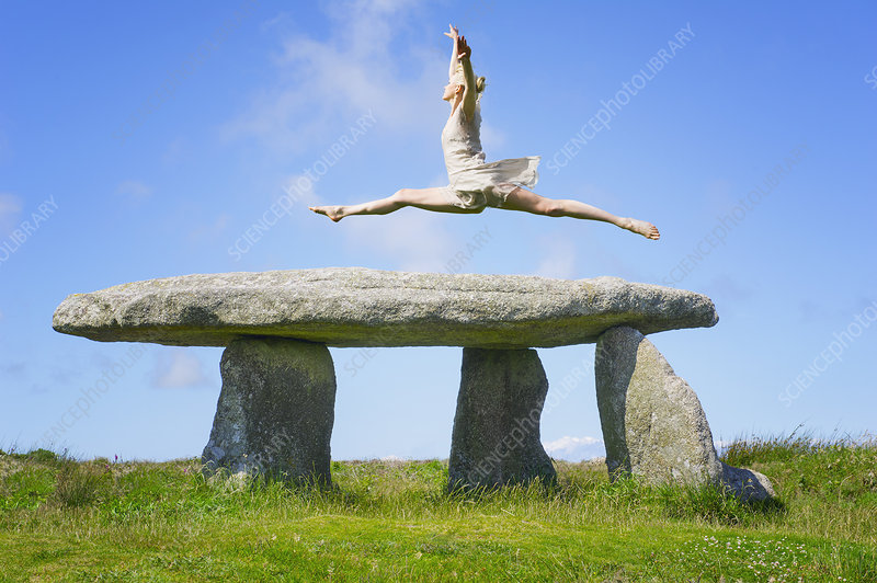 Dancer leaping over stone monument