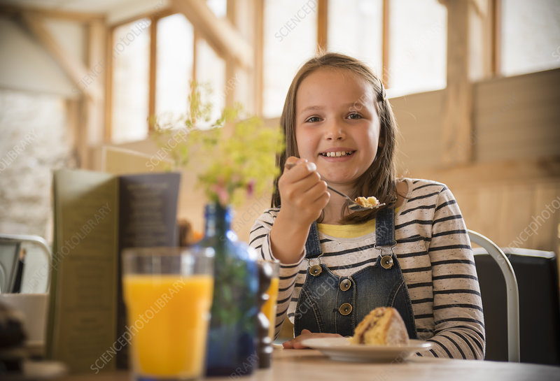 Girl eating cake in farm shop cafe