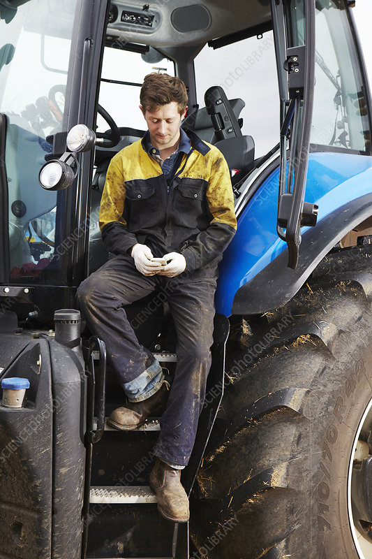 Farmer using cell phone on tractor