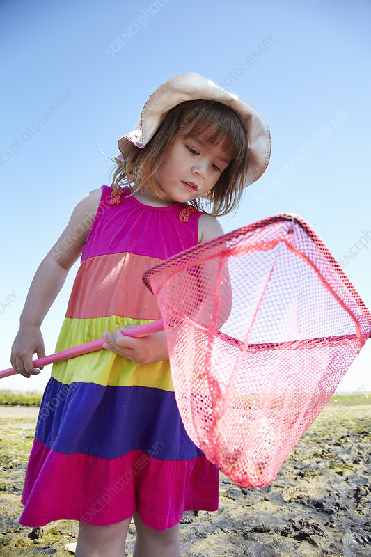 Girl examining fishing net outdoors